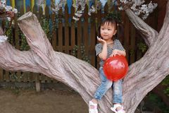 Cute naughty lovely adorable little girl play with balloon and sit by a tree have fun outdoor in summer park happy smile. A little Asian Chinese girl, have fun Royalty Free Stock Photography