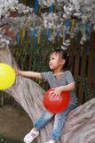 Cute naughty lovely adorable little girl play with balloon and sit by a tree have fun outdoor in summer park happy smile. A little Asian Chinese girl, have fun Royalty Free Stock Photo
