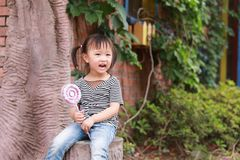 Cute naughty lovely adorable little girl play with lolipop and sit by a tree have fun outdoor in summer park happy smile. A little Asian Chinese girl, have fun Royalty Free Stock Photography