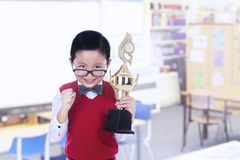 Cute nerd boy holding trophy at library Royalty Free Stock Photos
