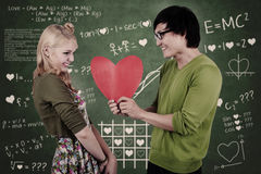 Cute nerd guy and girl holding heart in classroom Stock Photo