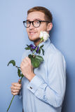 Cute nerd with a white rose. Date, birthday, Valentine Stock Photo