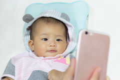 Cute new born baby looking mobile phone. Stock Photo