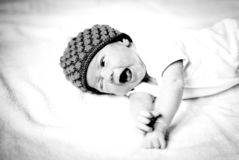 Cute newborn baby beanie lying on the bed black and white photo