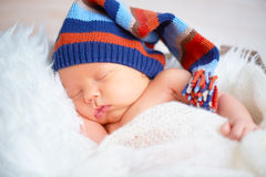 Cute newborn baby in blue knit cap sleeping in basket Royalty Free Stock Photos
