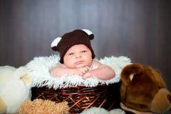 Cute newborn baby boy in basket with teddy bear hat, looking at. Camera, teddy bear toys around him stock photos