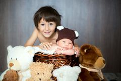 Cute newborn baby boy in basket with teddy bear hat, looking at Stock Photos