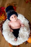 Cute newborn baby boy with knitted hat in a basket Royalty Free Stock Images