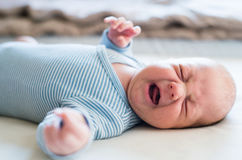 Cute newborn baby boy lying on bed, crying. Close up. stock photos