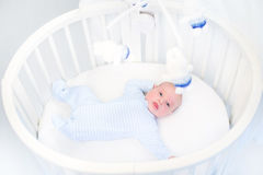 Cute newborn baby boy in round crib watching toys Stock Photography