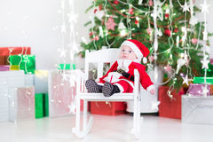 Cute newborn baby boy in Santa costume under Christmas tree Stock Image