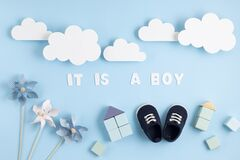 Cute newborn baby boy shoes with festive decoration over blue background. Baby shower, birthday, invitation or greeting card