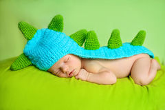 Cute newborn baby boy sleeping. On green cover in dinosaur costume stock image