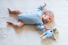 Cute newborn baby boy with teddy bear lying on bed Stock Photography