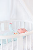 Cute newborn baby boy in white bed with canopy Royalty Free Stock Photography