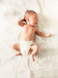 Cute newborn baby in diapers lying on white sheets on bed Royalty Free Stock Photo