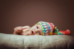 Cute newborn baby girl in Knit Hat. A cute little baby is looking into the camera and is wearing a Knit Hat hat. The baby could be a boy or girl and has blue Royalty Free Stock Photography