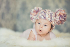 Cute newborn baby girl in knitted cap with bubonic Royalty Free Stock Images