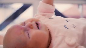 Crying two-month baby. Cute newborn baby girl lies at the bed. Charming girl moves her little hands and cries stock video footage