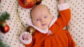 Cute newborn baby girl lies among Christmas toys stock video footage