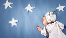 Cute newborn baby girl lying in the bed. 2 month old child in owl hat sleeping on blue blanket Royalty Free Stock Photos