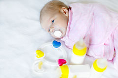 Cute newborn baby girl with nursing bottles and pacifier Royalty Free Stock Photos