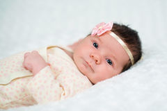 Cute newborn baby girl with pink bow Stock Photo