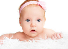 Cute  newborn baby girl with a pink flower ribbon Royalty Free Stock Images
