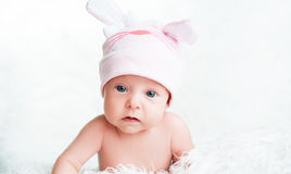 Cute newborn baby girl in a pink hat with ears Stock Photos