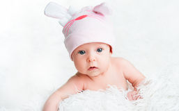 Cute newborn baby girl in a pink hat with ears Royalty Free Stock Photos