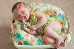 Cute newborn baby girl in a pink knit romper sleeping on a felted green blanket in a basket.  Royalty Free Stock Image