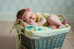 Cute newborn baby girl in a pink knit romper sleeping on a felted green blanket in a basket stock photos