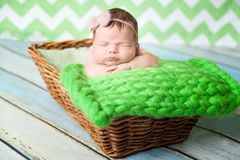 Cute newborn baby girl in a pink knit romper. Sleeping on a green chunky knit blanket in a basket Royalty Free Stock Photography