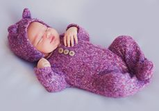 Cute newborn baby girl in purple knitted overall is sleeping peacefully stock image