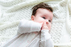 Cute newborn baby girl in romper suit lying on woolen blanket Stock Photography
