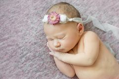 Newborn girl sleeping on her side in flower hairband, close-up Royalty Free Stock Images