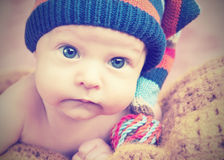 Cute newborn baby in knitted hat cap Stock Images