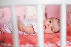 Cute newborn baby lying in bed Stock Photo