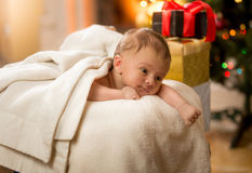 Cute newborn baby lying on stomach next to Christmas gifts Royalty Free Stock Image