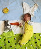 Cute newborn baby with rabbit ears playing with bunny toy feedin. G it with carrot Stock Images