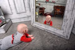 Newborn baby in red with gray clothes in front of the mirror looks at himself. Cute newborn baby in red with gray clothes in front of the mirror looks at himself royalty free stock photo