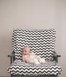 Cute newborn baby sitting in the big chair Stock Photo
