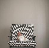 Cute newborn baby sitting in the big chair stock image