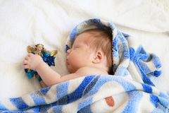 Cute newborn baby sleeping in blue blanket with figure of angel. In hands on white background Stock Photo