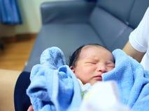Cute newborn baby sleeping in hands of parents. Stock Photo