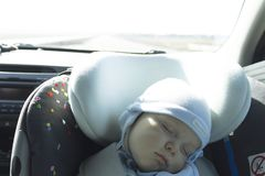 Cute newborn baby sleeping in modern car seat. Child new born traveling safety on the road. Safe way to travel fastened. Seat belts in a vehicle with young kids Royalty Free Stock Photography