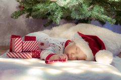 Cute newborn baby sleeping under Christmas tree near red gifts wearing Santa Claus hat stock photos