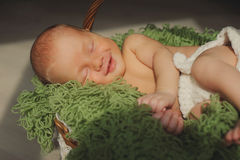 Cute newborn baby is  smling and sleeping in a basket. Royalty Free Stock Images