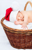 Cute newborn baby wearing Santa Claus hat sleeping in basket stock photo