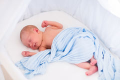 Cute newborn baby in white bed Royalty Free Stock Photos